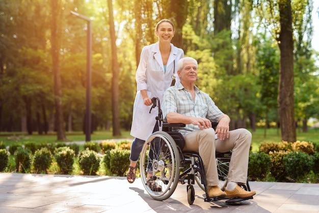 Lekarz ze staruszkiem na wózku inwalidzkim, chodzenie w słonecznym parku Premium Zdjęcia