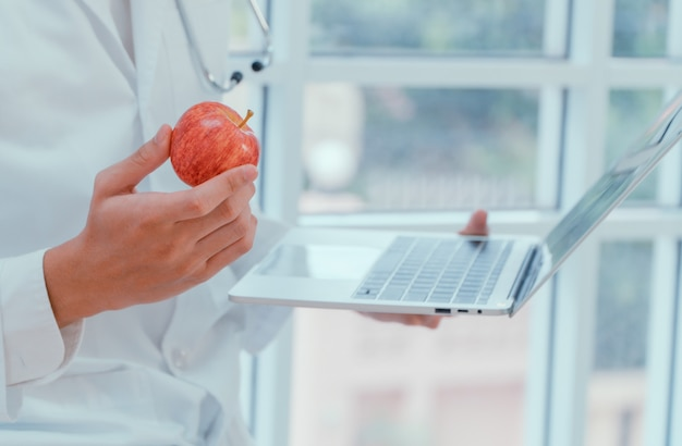 Lekarze Lub Dietetycy Trzymają Jabłka I Laptopy W Klinice Aby Wyjaśnić Zalety Owoców I Warzyw. Premium Zdjęcia