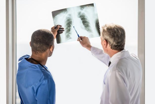 Lekarze patrząc na zdjęcie rentgenowskie trafiają do szpitala. Premium Zdjęcia