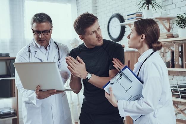 Lekarze Płci Męskiej I żeńskiej Z Stetoskopy W Biurze. Lekarze Pokazują Sportowcowi Na Laptopie. Premium Zdjęcia