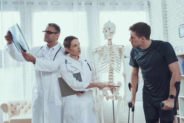 Lekarze pokazują miednicę rannemu sportowcowi. Premium Zdjęcia