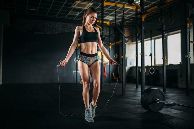 Lekkoatletka ćwiczenia Ze Skakanką W Sportowej Siłowni. Aktywna Kobieta Treningu W Klubie Fitness Premium Zdjęcia
