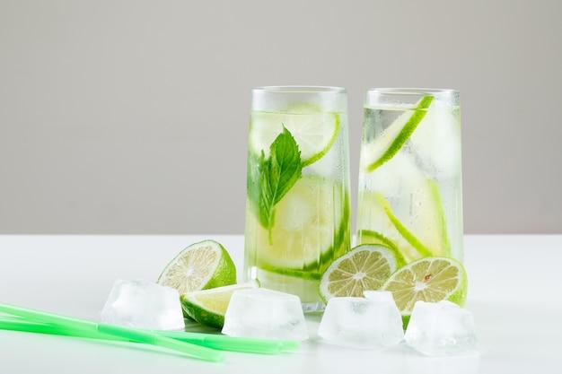 Lemoniada W Szklankach Z Cytrynami, Słomkami, Bazylią, Kostkami Lodu Widok Z Boku Na Białym I Szarym Darmowe Zdjęcia