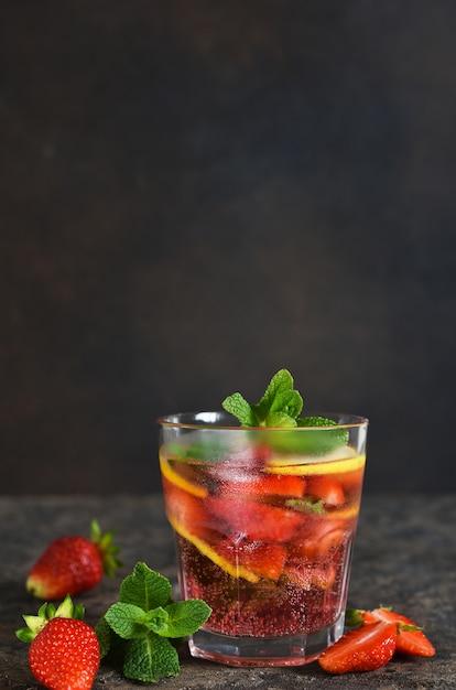 Lemoniada Z Truskawkami I Miętą Na Ciemnym Betonowym Stole. Premium Zdjęcia