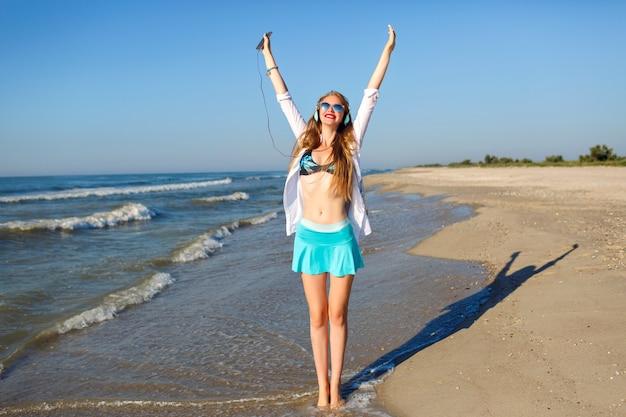 Letni Portret Szczęśliwej ładnej Dziewczyny, Która Bawi Się I Szaleje W Pobliżu Oceanu, Słoneczne Kolory I Pozytywny Klimat, Jasne Modne Stroje Plażowe, Słuchanie Muzyki Na Słuchawkach Darmowe Zdjęcia