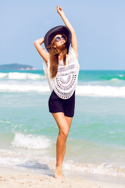 Letnia Moda Na Zewnątrz Portret Pięknej Eleganckiej Kobiety O Idealnym Ciele I Długich Nogach W Kapeluszu I Eleganckim Stroju Boho, Pozująca W Wietrzny Słoneczny Dzień Na Tropikalnej Plaży, Niesamowity Widok Na Ocean Darmowe Zdjęcia