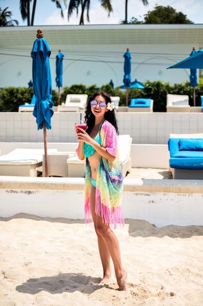 Letnie Pozytywne Wakacje Portret ładna Brunetka Kobieta Zabawy W Luksusowym Klubie Plażowym, Szczupłe Ciało, Modne Bikini I Kimono, Trzymając Napój Bezalkoholowy. Darmowe Zdjęcia