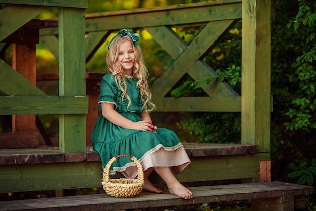 Letnie Wakacje Na Wsi. Portret Pięknej Dziewczyny W Zielonej Sukience, Która Siedzi Z Wiklinowym Koszem Na Schodach Drewnianej Werandy Premium Zdjęcia