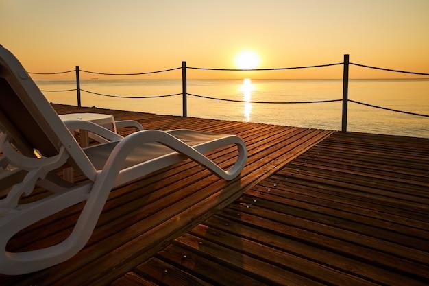 Leżak Na Plaży Stoi Na Drewnianym Molo Na Tle Spokojnego Morza I Wschodzącego Słońca Premium Zdjęcia