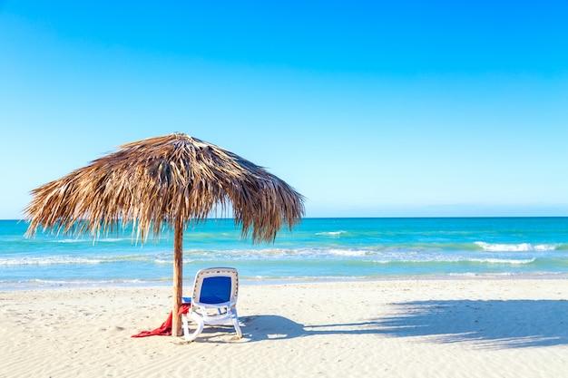 Leżak Pod Parasolem Na Piaszczystej Plaży Nad Morzem I Niebem. Premium Zdjęcia