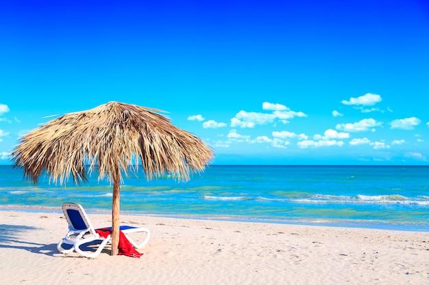 Leżak Pod Parasolem Na Piaszczystej Plaży Nad Morzem I Pochmurne Niebo. Premium Zdjęcia