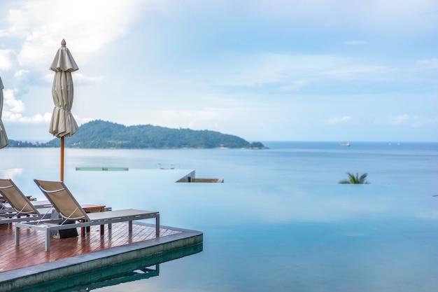 Leżaki I Basen Bez Krawędzi Z Pięknym Widokiem Na Morze. Premium Zdjęcia