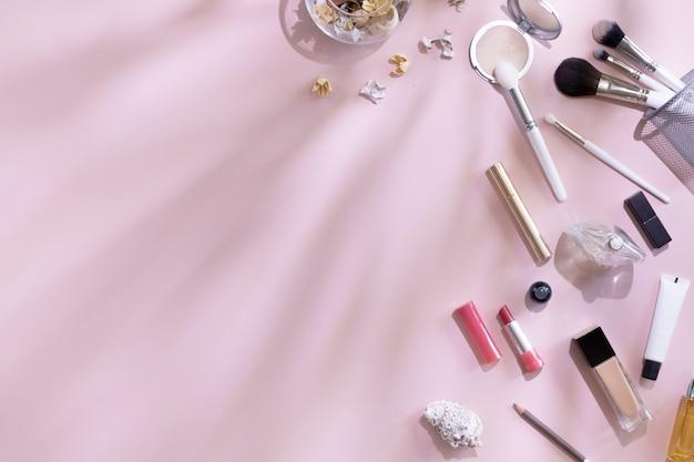 Leżał płasko i widok z góry produktów do makijażu i kosmetyków na różowym tle z liści cień i twarde światło, lato. koncepcja piękna dla blogera, pastelowe kobiety biurka biurka Premium Zdjęcia