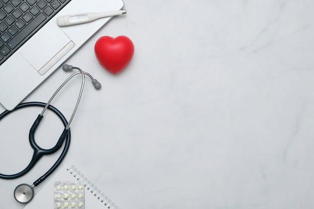 Leżał płasko z biurkowym stołem lekarza ze stetoskopem, notatnikiem, artykułami biurowymi i miejsca na kopię Premium Zdjęcia