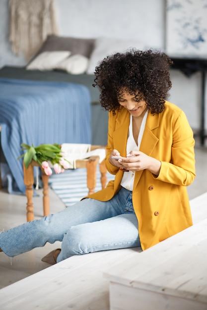 Lifestyle Concept - Portret Pięknej Kobiety Afroamerykanów Radosnego Słuchania Muzyki Na Telefonie Komórkowym. żółte Pastelowe Studio Tło. Kopiuj Przestrzeń. Premium Zdjęcia