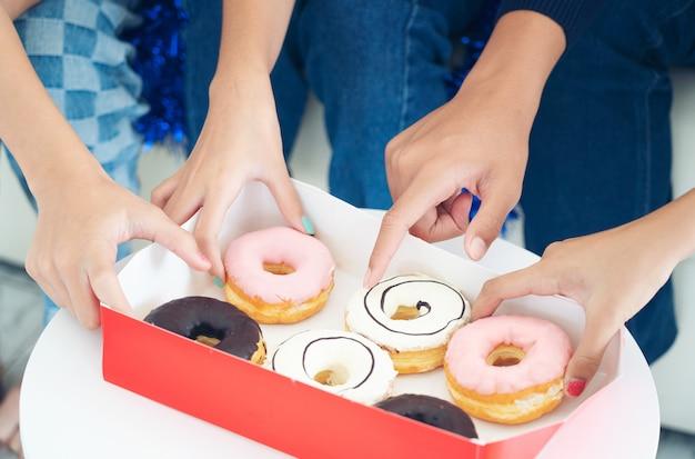 Lifestyle Friend Baw Się Z Donut, Grupa Rąk Trzymających Słodzący Deser Z Pączków, Przyjaźń, Koncepcja Pokoju. Premium Zdjęcia