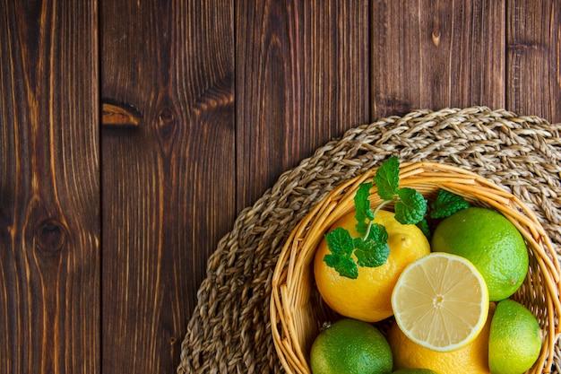 Limonki Z Cytrynami, Zioła W Wiklinowym Koszu Na Drewnianym Stole Darmowe Zdjęcia