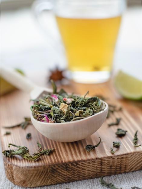 Liście Zielonej Herbaty W Drewnianą łyżką Z Plasterkami Limonki I Kubek Parzonej Herbaty Na Podłoże Drewniane Lub Powierzchni, Zbliżenie Premium Zdjęcia