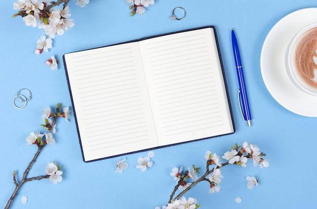 Lista życzeń Na Przyszłe Plany. Kompozycja Leżąca Płasko Z Kwiatami, Notatnikiem I Kawą Premium Zdjęcia