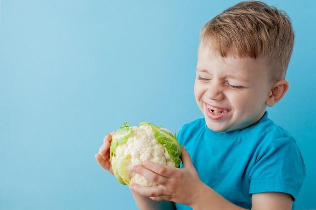 Little Boy Trzyma Brokuły W Jego Rękach Na Błękitnym Tle, Diecie I ćwiczeniu Zdrowie Pojęcia Na Dobre Premium Zdjęcia