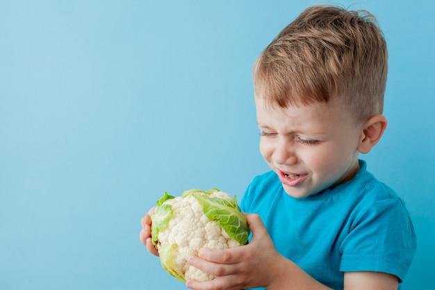 Little boy trzyma brokuły w jego rękach na błękitnym tle Premium Zdjęcia
