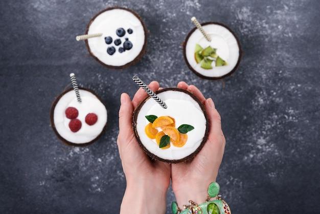 Lody W Miseczkach Kokosowych Z Jagodami W Ręku Na Szaro Premium Zdjęcia