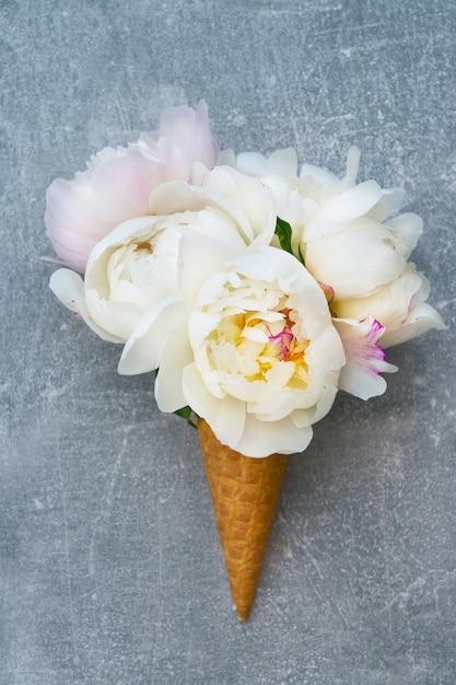 Lody waflowe z białymi kwiatami piwonii na szaro. Premium Zdjęcia