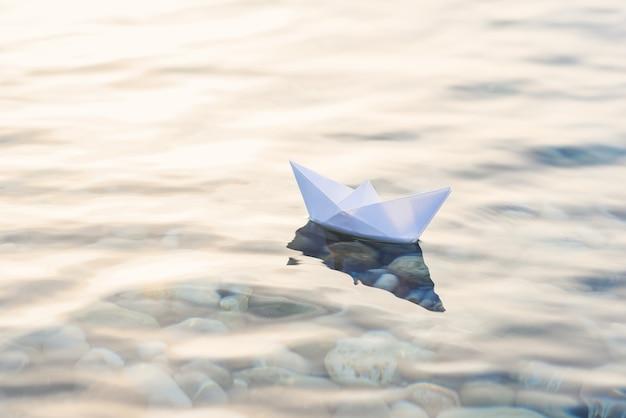 Łódź Origami Białego Papieru Na Niebieskiej Głębokiej Wodzie. Premium Zdjęcia