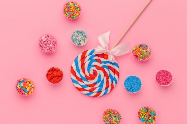 Lollipop I Cukier Kropimy W Papierowych Pucharach Na Różowym Tle, Odgórny Widok Premium Zdjęcia