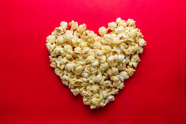 Love cinema koncepcji popcorn ułożone w kształcie serca na czerwonym tle Premium Zdjęcia