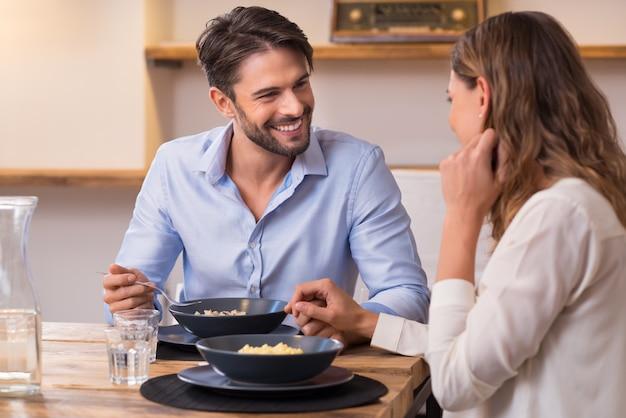 Loving Para Patrząc Na Siebie Podczas Lunchu. Bliska Strzał Młodego Mężczyzny I Kobiety Obiad W Domu. Szczęśliwa Młoda Para Jedzenie. Premium Zdjęcia