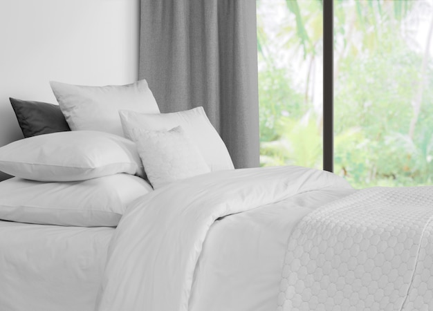 Łóżko z pościelą na oknie z szarymi zasłonami. Premium Zdjęcia