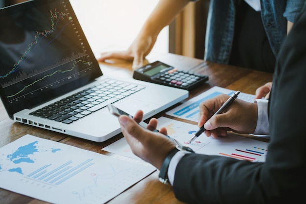 Ludzie Biznesu Omawiają Wykresy I Wykresy Pokazujące Wyniki Udanej Pracy Zespołowej. Analizują Wykresy Inwestycyjne Za Pomocą Laptopa Premium Zdjęcia