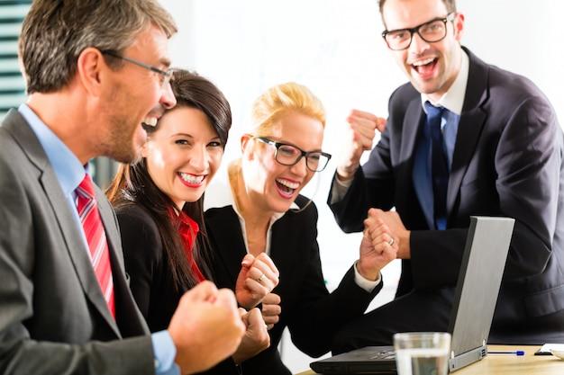 Ludzie biznesu patrzeje laptop z sukcesem Premium Zdjęcia