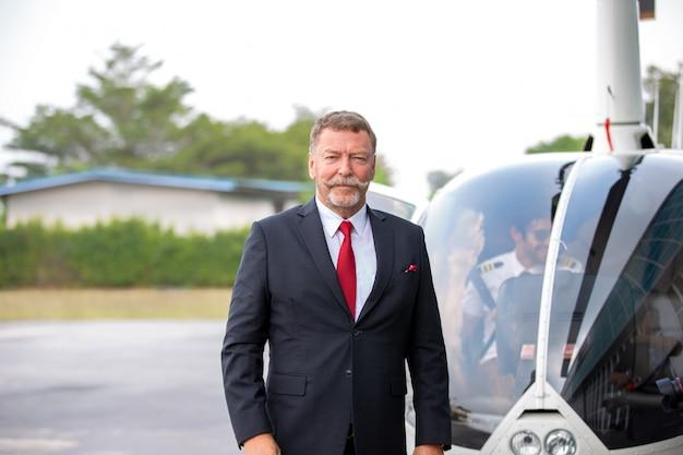 Ludzie Biznesu Podróżujący Helikopterem, Strzał Dojrzałego Biznesmena Za Pomocą Zestawu Słuchawkowego Podczas Podróży Helikopterem Premium Zdjęcia
