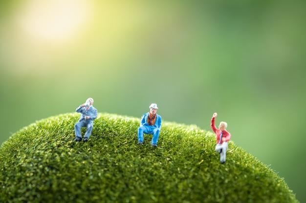 Ludzie biznesu siedzą na zielonym mchu. Premium Zdjęcia
