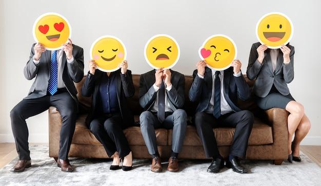 Ludzie biznesu siedzi wraz z ikonami Premium Zdjęcia