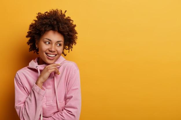 Ludzie, Koncepcja Stylu życia. Pozytywna Ciemnoskóra Kobieta Szczęśliwa, że Znajduje Dobre Okazje Do Przyszłej Pracy, Trzyma Podbródek Z Szerokim Uśmiechem, Słyszy Wspaniałe Wiadomości, Jest Optymistyczna, Pozuje Na żółtej ścianie Darmowe Zdjęcia