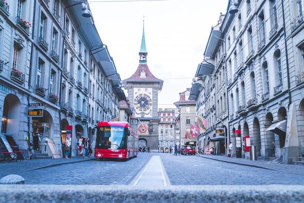 Ludzie na alei handlowej z wieżą zegarową astronomiczną zytglogge w bernie w szwajcarii Premium Zdjęcia