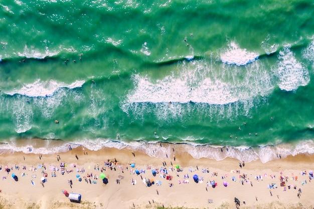 Ludzie Na Plaży I Ludzie Pływający W Morzu Premium Zdjęcia