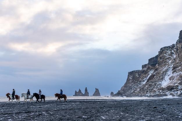 Ludzie Odchodzą Konno Po Czarnej Plaży Atlantyku Na Reynisfjara Premium Zdjęcia