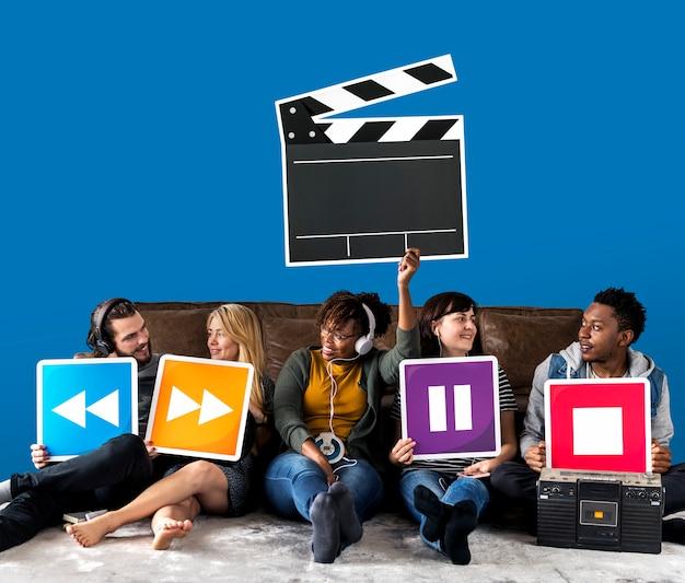 Ludzie posiadający ikony odtwarzacza multimedialnego i ikona klapy Darmowe Zdjęcia