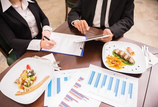 Ludzie pracujący nad strategią marketingową podczas lunchu biznesowego. Premium Zdjęcia