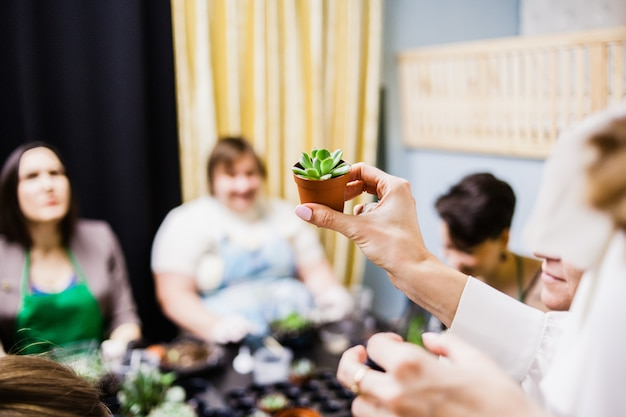Ludzie Są Wyrzucani Z Rośliny, Rękawiczki I Sukulenty Premium Zdjęcia