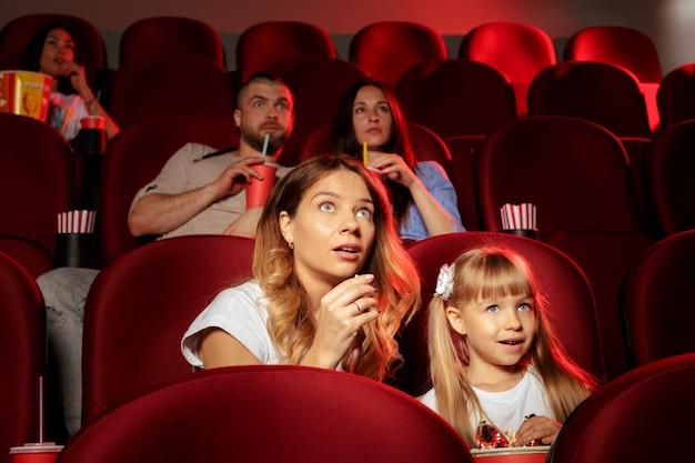 Ludzie siedzący w kinie z popcornem i napojami Premium Zdjęcia