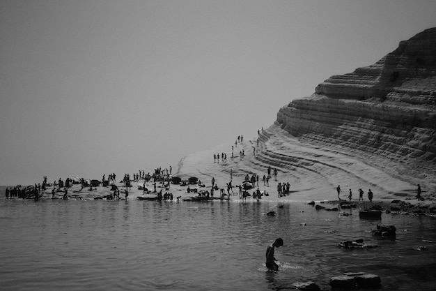 Ludzie Spędzający Dzień Na Plaży W Pobliżu Skalistego Wzgórza Darmowe Zdjęcia