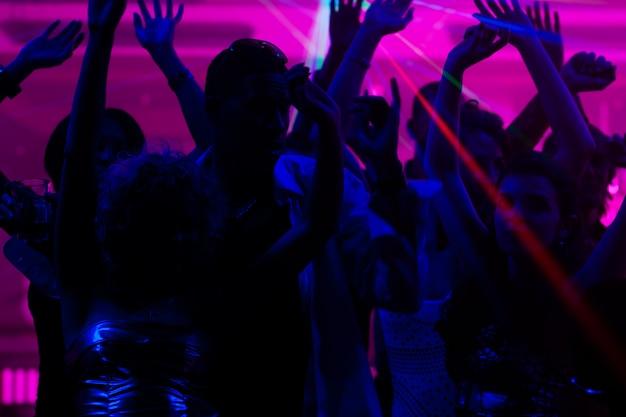 Ludzie tańczą w klubie z laserem Premium Zdjęcia