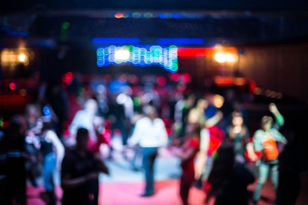 Ludzie tańczą w nocnym klubie rozmazane tło. piękni zamazani światła na parkiecie tanecznym Premium Zdjęcia