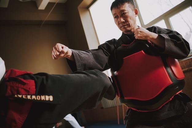 Ludzie Trenują Ze Sprzętem Ochronnym W Pokoju Sportowym. Premium Zdjęcia