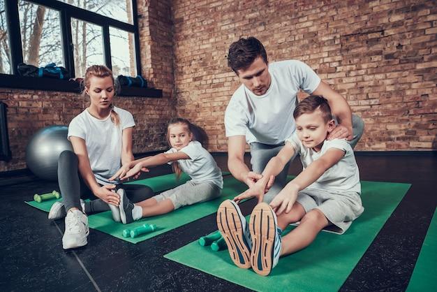 Ludzie uczą dzieci rozciągających się na siłowni Premium Zdjęcia